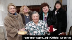 Представники керченської влади вручили жінці похилого віку, яка пережила блокаду Ленінграда, батон і медаль