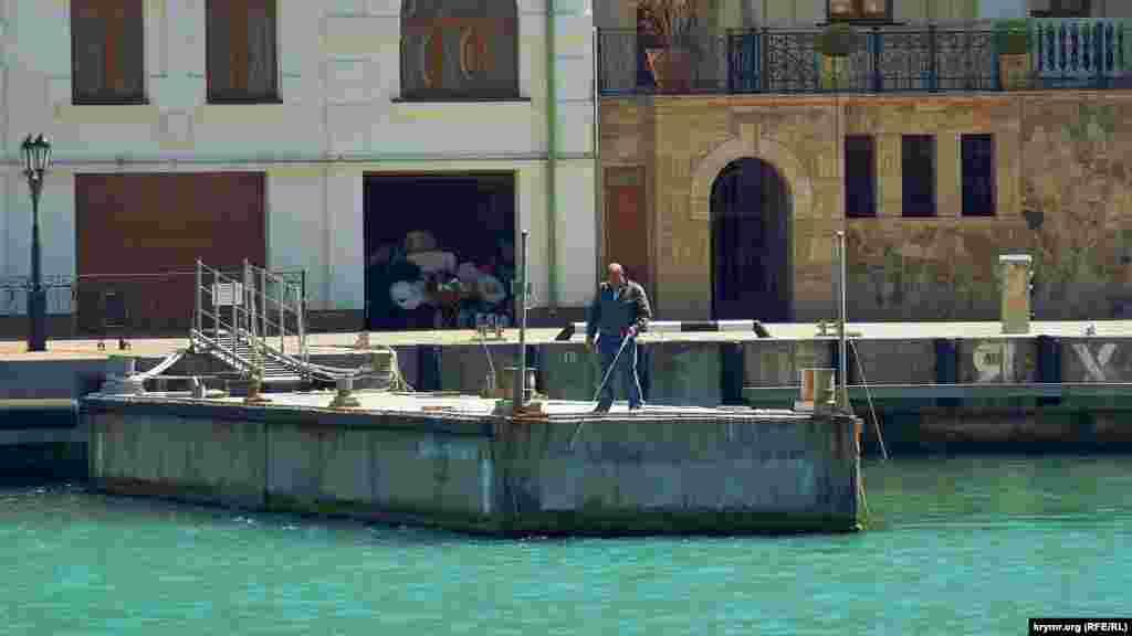 Мужчина ловит рыбу с пирса