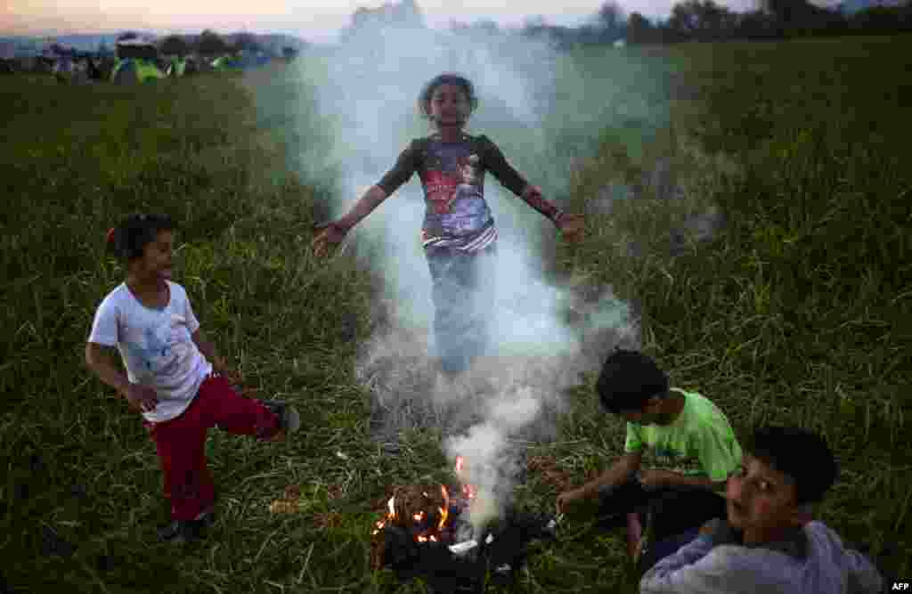 Children gather around a campfire in a makeshift camp at the Greek-Macedonian border near the Greek village of Idomeni, where over 11,000 refugees and migrants are currently stranded by the Balkan border blockade. (AFP/Bulent Kilic)