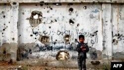 Сирийский ребенок с игрушечным оружием на фоне простреленной стены в пригороде Дамаска, 13 апреля 2017
