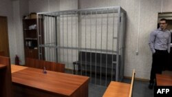 An employee stands near the empty defendant's dock in the Tverskoi district court in Moscow where the posthumous trial of Sergei Magnitsky was begun and immediately postponed for 10 days on March 11.