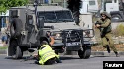 Pamje e sulmit të një palestinezi i veshur si reporter duke e therrë me thikë një ushtar izraelit, derisa ushtari tjetër e vranë sulmuesin në Hebron të Bregut Perëndimor më 16 tetor