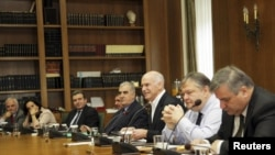 Greek Prime Minister George Papandreou (center), who has agreed to step down, holds an emergency cabinet meeting at the parliament in Athens on November 8.