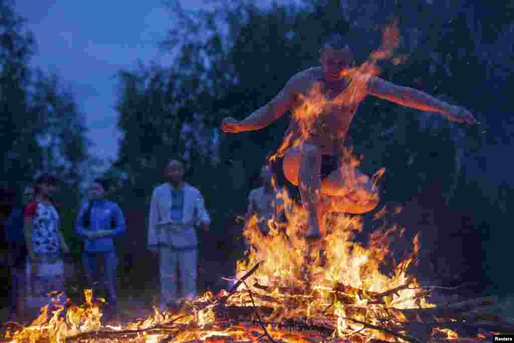 A man jumps over a campfire during a celebration of the traditional Ivana Kupala (Ivan the Bather) holiday near Omsk, Russia. The ancient tradition, originating from pagan times, is usually marked with grand overnight festivities. During the Ivana Kupala, people jump over burning campfires and bathe in a lake or a river, as they believe it will purge them of their sins and make them healthier. (Reuters/Dmitry Feoktistov)
