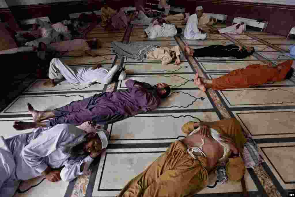 Muslim men rest in the heat at a mosque in Peshawar.