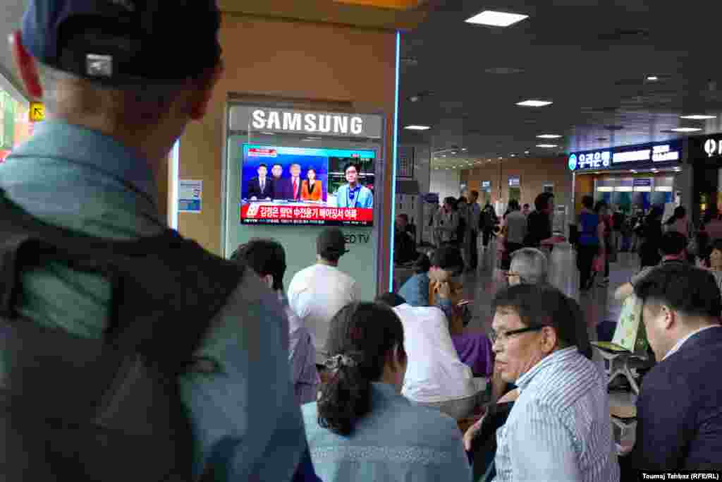 Люди следят за ходом переговоров Дональда Трампа и Ким Чен Ына по телевидению. Южная Корея, Сеул.