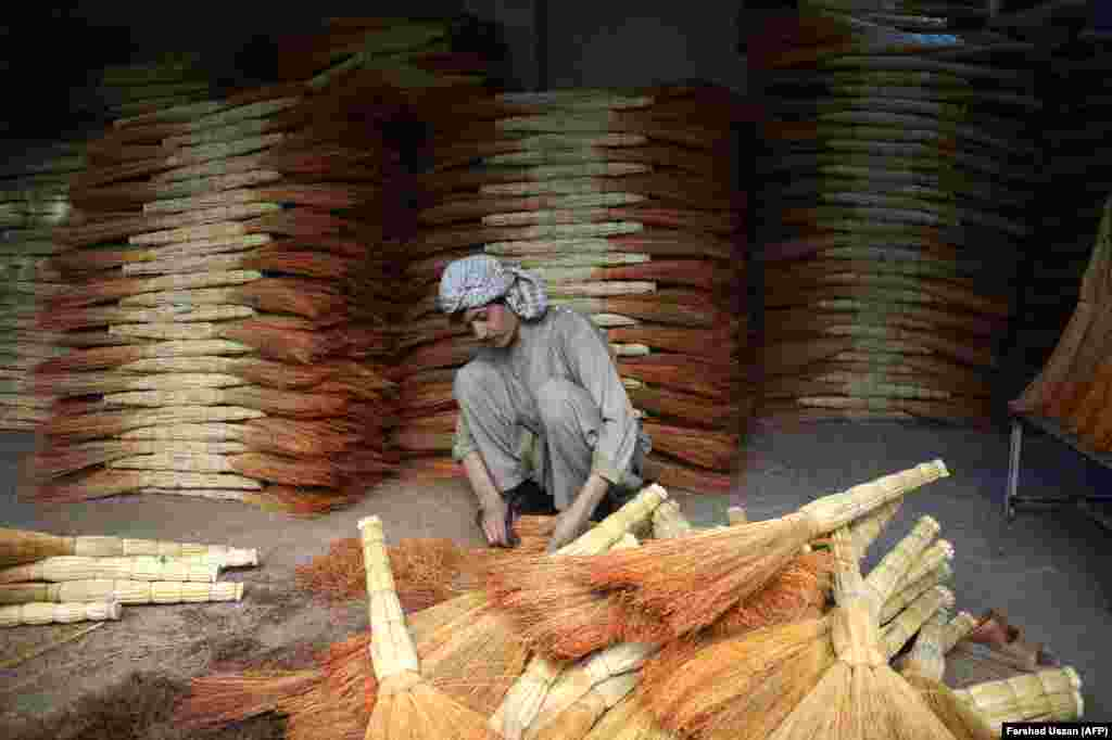 Afghan shopkeeper Naeem, 32, sorts brooms in his shop as he waits for customers on the outskirts of the northern city of Mazar-e Sharif. (AFP/Farshad Usyan)