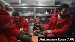 Syrian staff from the International Committee of the Red Cross take part in an evacuation operation in Douma in the eastern Ghouta region on the outskirts of the Syrian capital, Damascus, on December 26.