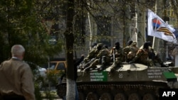 Ukraine -- Men wearing military fatigues ride on an armoured personnel carrier (APC) outside the regional state building seized by pro-Russian separatists in the eastern city of Slovyansk, April 18, 2014
