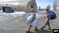 U.S. servicemen carry bags as they dismantle a tent camp at the U.S. transit center at Manas on March 6.