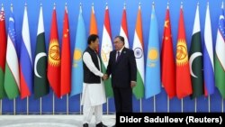 Tajik President Emomali Rahmon (right) shakes hands with Pakistani Prime Minister Imran Khan during the Shanghai Cooperation Organization (SCO) summit in Dushanbe on September 17.