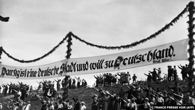 """На фотографии, датированной 1939 годом, изображены люди, отдающие фашистское приветствие под нацистским знаменем с лозунгом Гитлера, провозглашающим, что польский город """"Данциг (Гданьск) является немецким городом и хочет принадлежать Германии"""""""