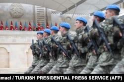 Katonák vonulnak el a két vezető előtt.