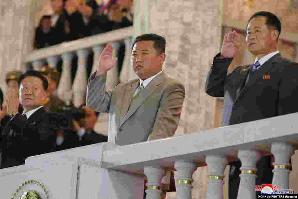 Kim Dzsongun (középen) nézi a katonai parádét 2021. szeptember 8-án Phenjanban