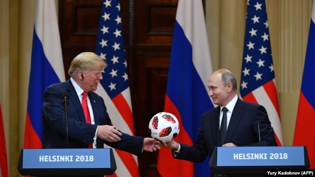 Russian President Vladimir Putin (right) offers a ball from the 2018 soccer World Cup to U.S. President Donald Trump during a joint press conference after a meeting in Helsinki in July 2018.