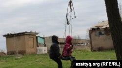 Внук и внучка Тамары Сейсеновой играют на территории заброшенного склада. Шымкент, 30 марта 2017 года.