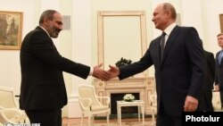 Armenian Prime Minister Nikol Pashinian (left) shakes hands with Russian President Vladimir Putin at a meeting in Moscow in June.