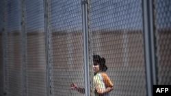 O fată din Siria în spatele gardului care înconjoară adăpostul pentru imigranți clandestini de la Liubimeț, Bulgaria