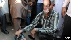 A cobbler wearing a mask of British author Salman Rushdie polishes shoes outside a mosque during a protest by an Islamic organization in Mumbai on January 11, ahead of the planned visit.