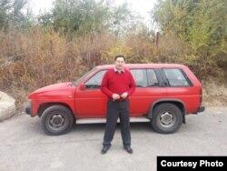 Ермек Нарымбаев позирует у своей машины, когда она еще была цела.