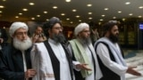 FILE: Mullah Abdul Ghani Baradar, the Taliban group's top political leader, second from left, arrives with other members of the Taliban delegation for talks in Moscow in May.