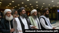 FILE: Mullah Abdul Ghani Baradar, a top Taliban leader, second from left, arrives for talks in Moscow in May 28.