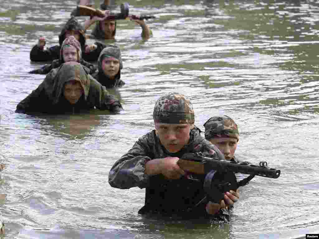 Teenagers undergo training at a military boot camp run by local Cossack organizations and set up in the mountains of Crimea near the town of Bakhchisarai. Some 100 youngsters from Russia, Belarus, and Ukraine, as well as the Georgian breakaway regions of Abkhazia and South Ossetia, have taken part in the training course, which lasts for about a month and includes mountaineering, martial arts, and survival techniques.Photo by Gleb Garanich for Reuters