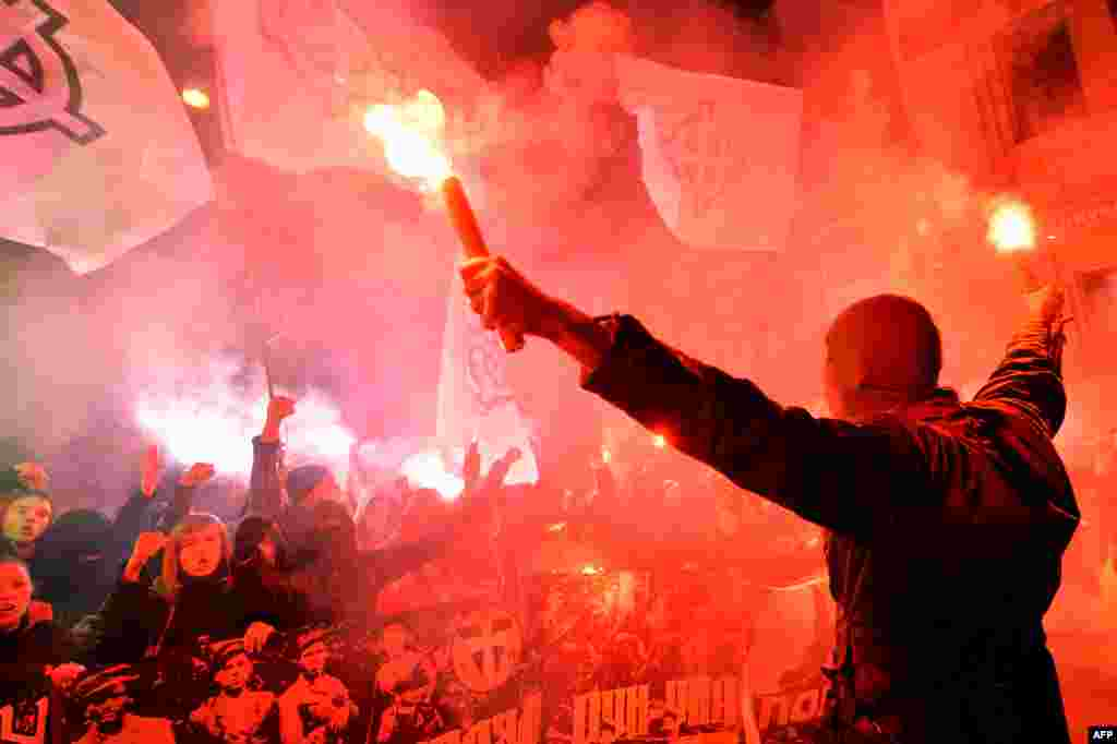 Young Ukrainian ultranationalists hold flares and shout slogans during a march in Kyiv. (AFP/Sergei Supinsky)