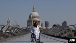 Британский баскетболист-паралимпиец Аде Адепитан везет олимпийский огонь по Мосту тысячелетия. Лондон, 26 июля 2012 года.