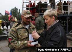 Мария Подыбайло с военным рассматривает государственную награду бойца