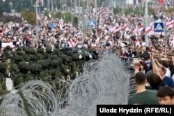 Security forces standing behind barbed wire observe protesters during another mass rally in Minsk on August 23.