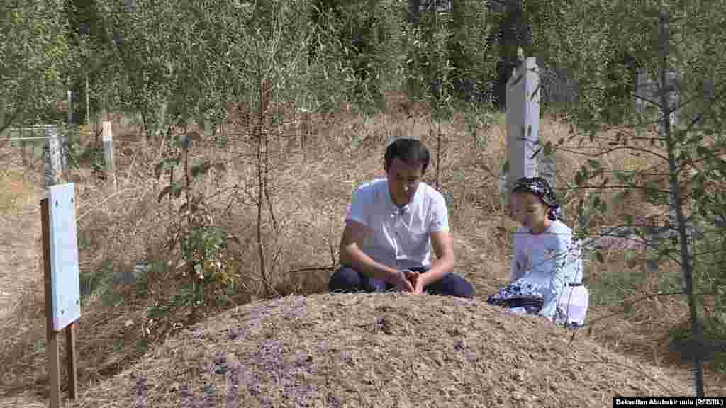 Брат погибшего Шахрух и дочь Зулайка на могиле Алишера Саипова.
