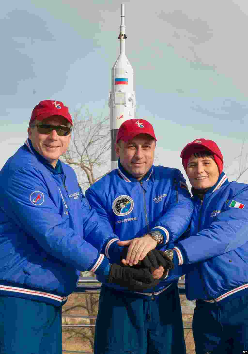 U.S. astronaut Terry Virts (left), Russian cosmonaut Anton Shkaplerov (center), and the European Space Agency's Italian astronaut Samantha Cristoforetti pose in front of the Soyuz TMA-15M space vehicle at its launch pad in Kazakhstan. The three are due to blast off for the International Space Station on November 23. (AFP)