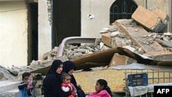 An Iraqi family sits outside its destroyed home in Diyala in March 2008