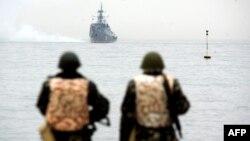 Украинские солдаты смотрят на российский военный корабль, выплывающий из порта Севастополя. 4 марта 2014 года.