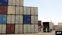 Iranian workers transfer goods from a cargo container to trucks at the port in the city of Chabahar.