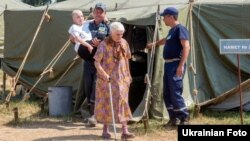 Internally displaced Ukrainians are assisted at a temporary camp for people from Svatovo, in Luhansk region, on August 12.