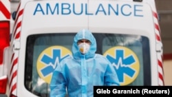 A medical worker wearing protective gear stands next to an ambulance outside a hospital for patients infected with the COVID-19 in the Ukrainian capital, Kyiv. (file photo)