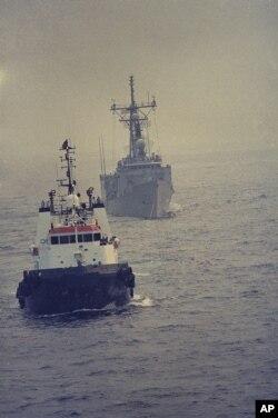 یک کشتی مینروب کویتی، پس از برخورد ناو ساموئل رابرت با مین، در حال انتقال آن به دوبی است.