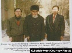 Кытайлык кыргыздардын залкар манасчысы Жусуп Мамай кыргызстандык Орозбүбү Сатиш кызы жана артыштык илимпоз Мамбеттурду Мамбетакун (сол жакта) менен. Үрүмчү шаары, 1997-жылдын ноябры.