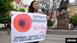 Дівчина тримає плакат із зображенням червоного маку – символу пам'яті жертв усіх воєн, починаючи із Першої світової війни (1914–1918). Львів. Архівне фото