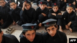Boys attend a class at a school in a tribal agency in Pakistan's rugged northwest, where the goverment's battle with militants has destroyed the local econmy.