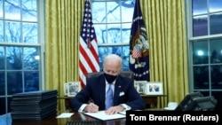 Президент США Джо Байден во время подписания указов в Овальном кабинете после своей инаугурации. Вашингтон, 20 января 2021 года.