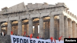 A giant banner protesting Greece's austerity measures hangs near the Parthenon on Acropolis hill in Athens.