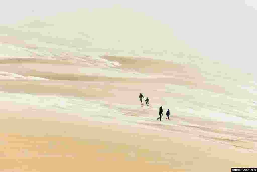 People walk on the partially snow-covered Pilat (or Pyla) sand dune after a snowfall on February 28 in La Teste-de-Buch, southwestern France. (AFP/Nicolas Tucat)