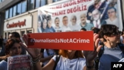 A journalist holds up a banner outside the headquarters of opposition newspaper Cumhuriyet in Istanbul during a protest in July.