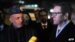 Afghan President Hamid Karzai (left) and German Foreign Minister Guido Westerwelle speak to reporters upon Karzai's arrival in Germany for the Bonn II conference on December 5.