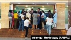 Группа матерей, требующих улучшения социального положения многодетных, и представители городской администрации у здания столичного акимата. Нур-Султан, 5 августа 2019 года.