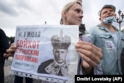 "A woman holds a poster reading ""July 1. Boycott Of Putin's Amendments!"" during a protest in St. Petersburg on July 1."