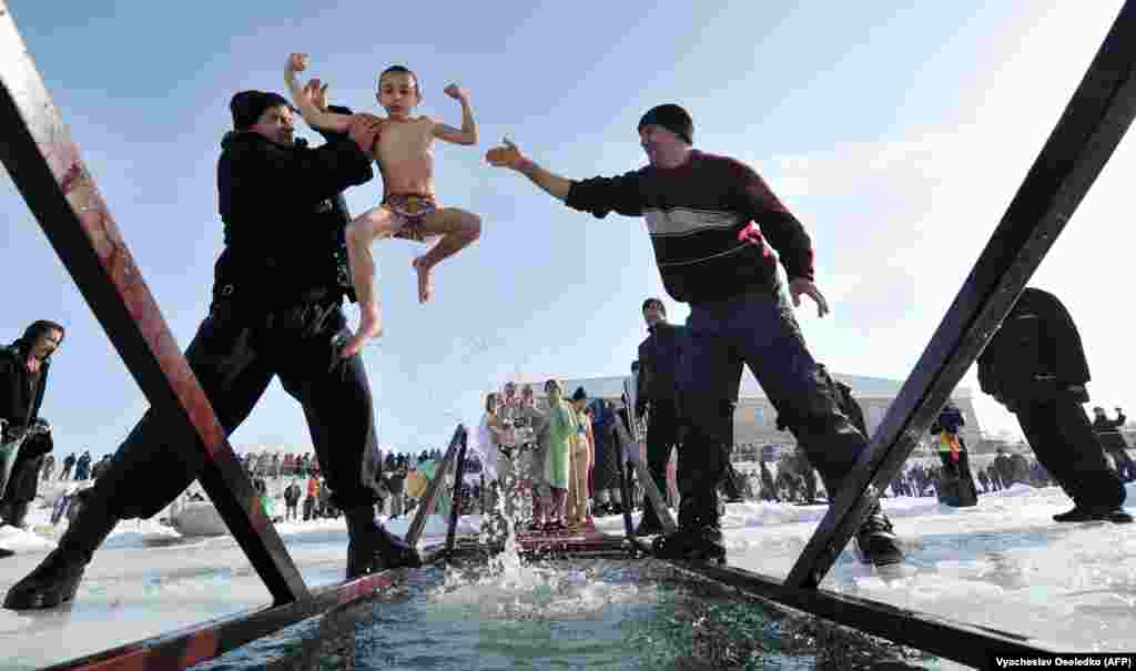 Assistants help an Orthodox Christian boy take a dip in icy water in the village of Leninskoe, near the Kyrgyz capital, Bishkek, on January 19. The ritual is part of the celebration of Epiphany, marking the baptism of Jesus by John the Baptist.